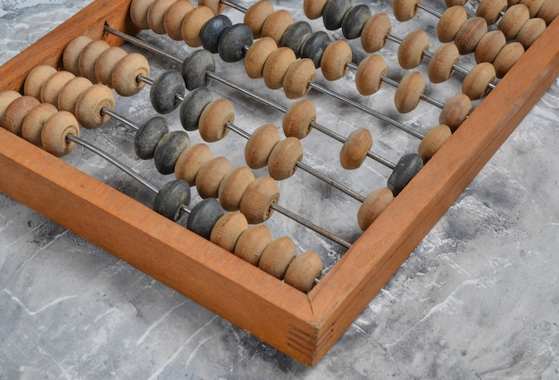 Ancient wooden abacus on a gray concrete surface