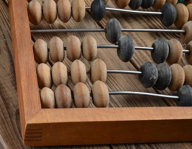 Ancient wooden abacus on a rustic wooden table