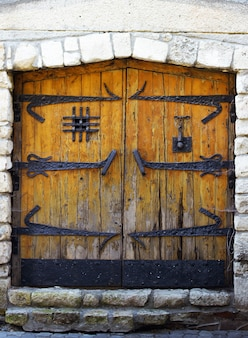 Древняя деревянная дверь в старой каменной стене замка.