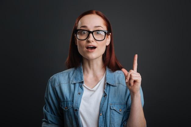 그리고 당신은 그것을 알고 있습니까? 그녀의 요점을 설명하고 회색 배경에 고립 된 서있는 동안 그녀의 손가락을 가리키는 지속적 근면 좋은 여자