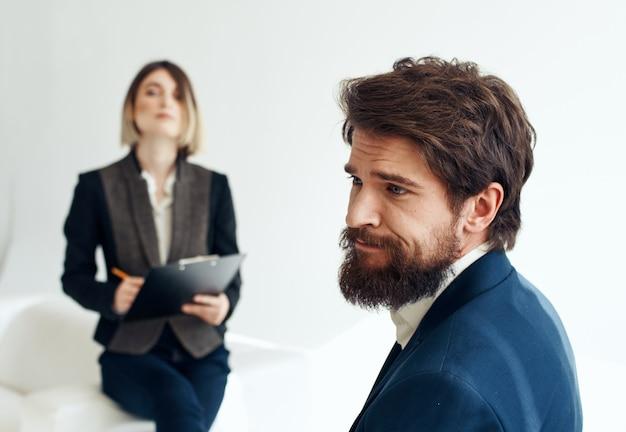 И эмоциональный мужчина на собеседовании и бизнес-леди в костюме на заднем плане. фото высокого качества