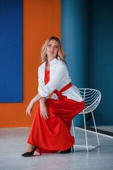 또한 편안합니다. 축제 빨간 드레스의 아름다운 금발은 주황색과 파란색 벽과 흰색 의자가있는 방에 있습니다.