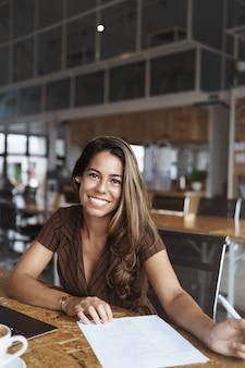 И успешная латиноамериканская женщина улыбается, работает в кафе