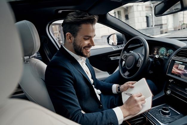 그리고 만나러 가는데... 정장 차림의 잘생긴 청년이 개인용 수첩에 뭔가를 적고 차 안에 앉아 웃고 있다