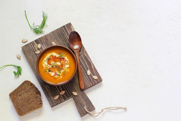 ローストしたカボチャとニンジンのスープ、クリーム、黒胡and、カボチャの種、まな板、新鮮なカボチャのスライス、黒パン