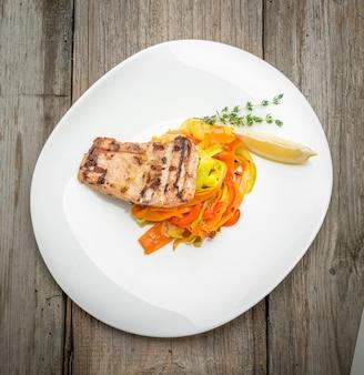 揚げ魚のandと木製の背景に新鮮な野菜サラダ。