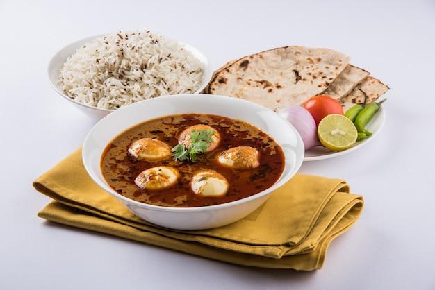 アンダカレーまたはエッグマサラグレイビー、インドのスパイシーな料理またはレシピ、ジェラライス、ロティまたはナン、セレクティブフォーカスを添えて。カラフルまたは木製のテーブルトップの上