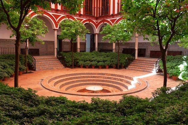 中央に円形の階段状の噴水があるアーチと柱に囲まれたアンダルシアの中庭