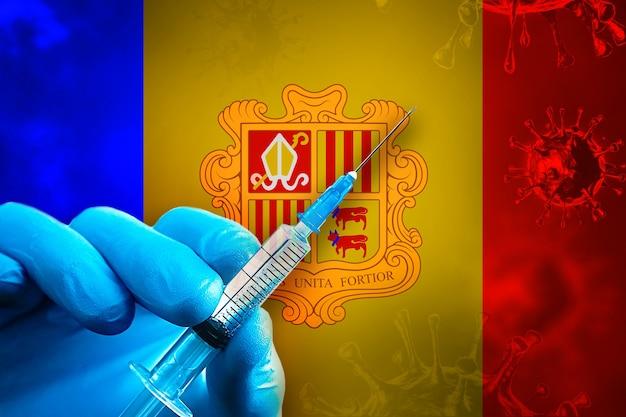 안도라 코비드19 예방 접종 캠페인 파란색 고무 장갑을 끼고 깃발 앞에 주사기를 들고 있습니다