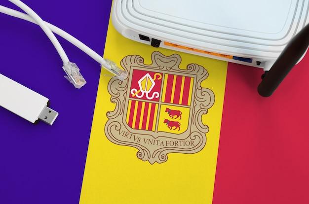 Флаг андорры изображен на столе с помощью интернет-кабеля rj45, беспроводного usb-адаптера wi-fi и маршрутизатора. концепция интернет-связи