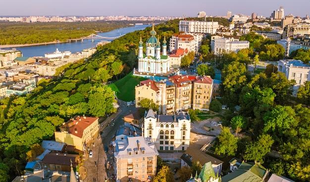 聖アンドリュー教会と上からandreevska通り、日没のポドル地区の街並み、キエフ(キエフ)、ウクライナの街のスカイラインの空中ドローンビュー
