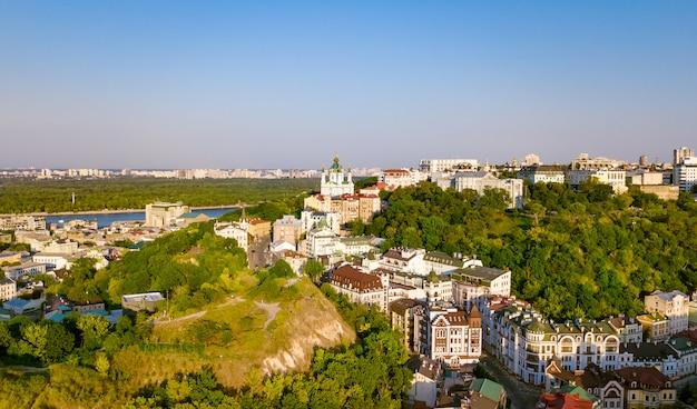 聖アンドリュー教会と上からandreevska通り、日没のポドル地区の街並み、キエフ(キエフ)、ウクライナの街のスカイラインの空中のトップビュー