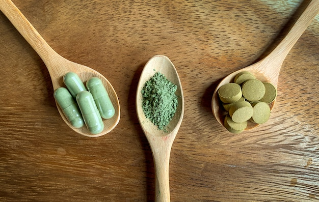 Andrographis paniculata, capsules and powder form on a wooden spoon