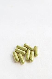 Закройте зеленое растительное лекарственное средство в капсулах от andrographis paniculata, здоровое растительное лекарственное средство из натурального продукта,