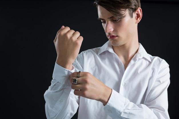 Андрогинный мужчина поправляет наручники