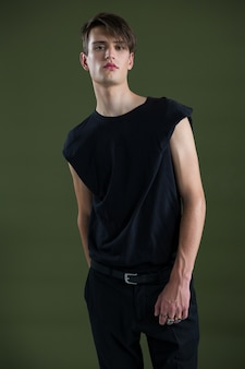 Androgynous man on black wall