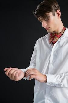 Androgynous man buttoning his shirt sleeve