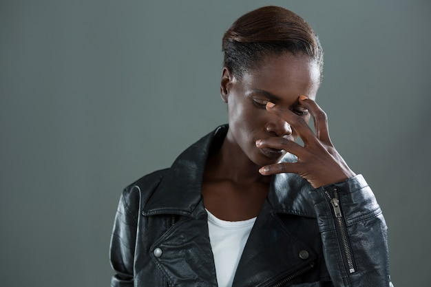 Androgynous man covering his face