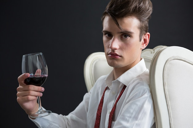 Androgynous man holding wine glass against black wall