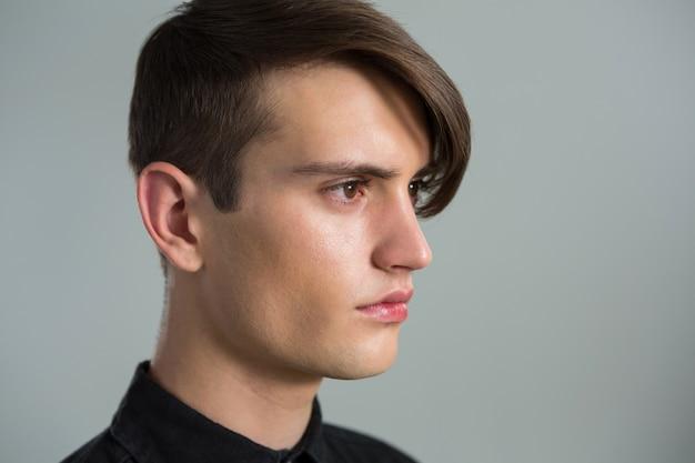 Androgynous man looking sideways against grey wall
