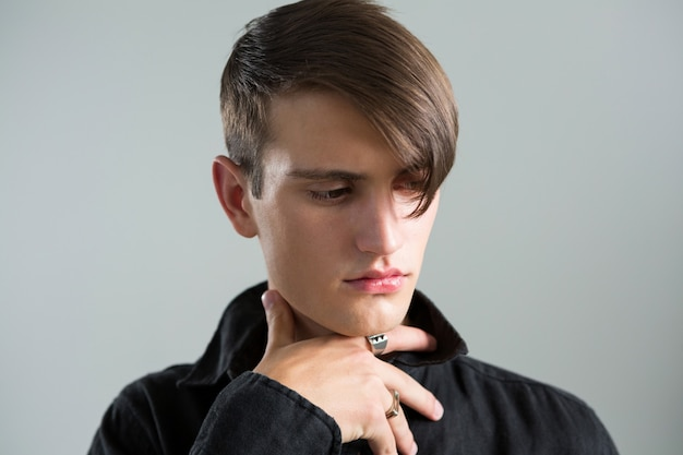 Androgynous man posing against grey wall