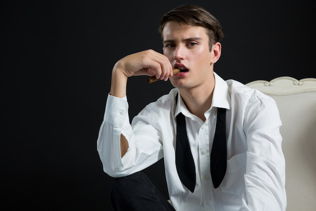 Androgynous man posing with cigar in his mouth