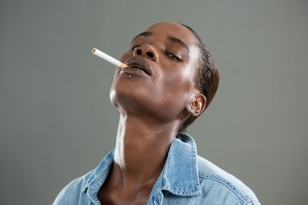 Androgynous man posing with cigarette in his mouth