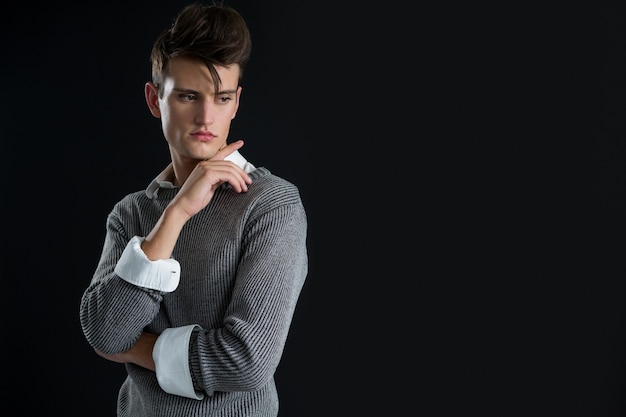 Androgynous man posing with hand on chin