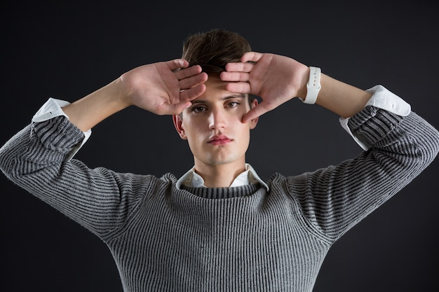 Androgynous man posing with hands on forehead