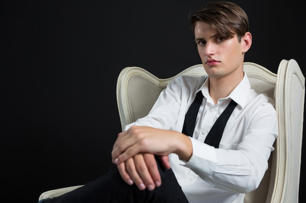 Androgynous man sitting on chair against black wall