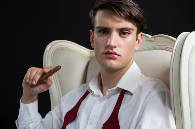 Androgynous man sitting on chair with cigar against black wall
