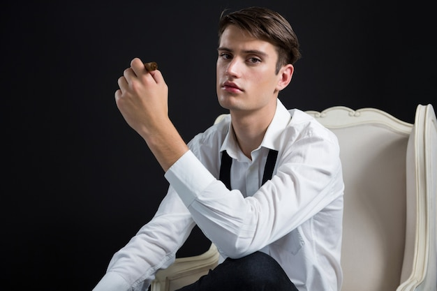 Androgynous man sitting on chair with cigar