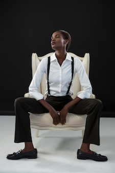 Androgynous man sitting on a chair