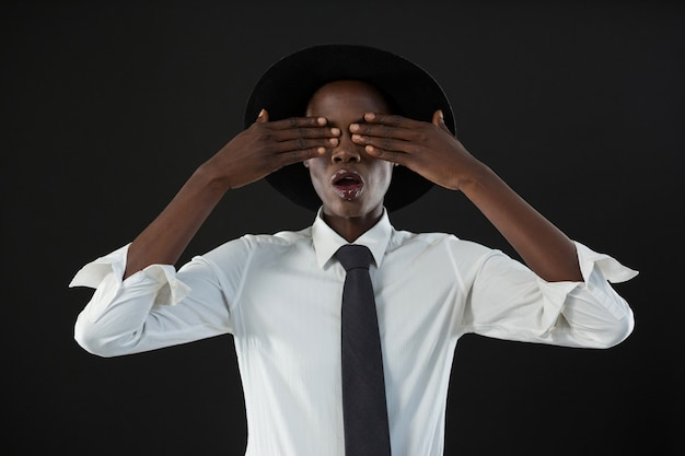 Androgynous man standing with his hands on eyes