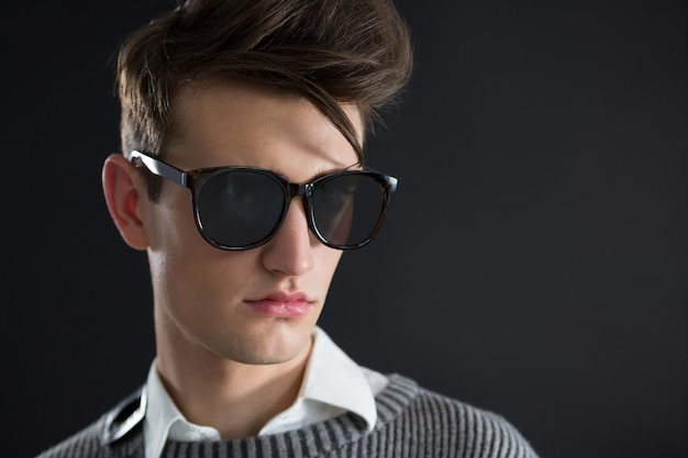 Androgynous man in sunglasses posing against black wall