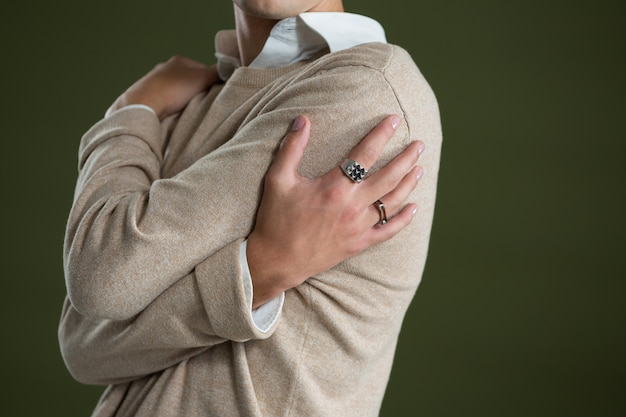Androgynous man touching his body against green wall