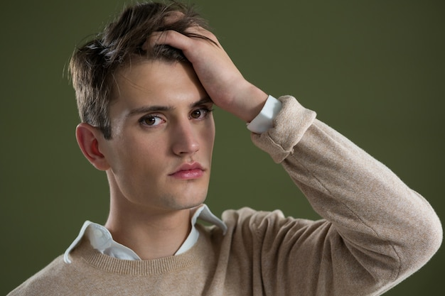 Androgynous man touching his hair against green wall