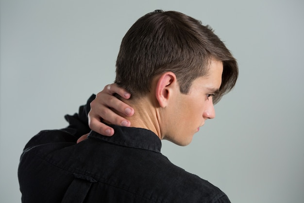 Androgynous man touching his neck