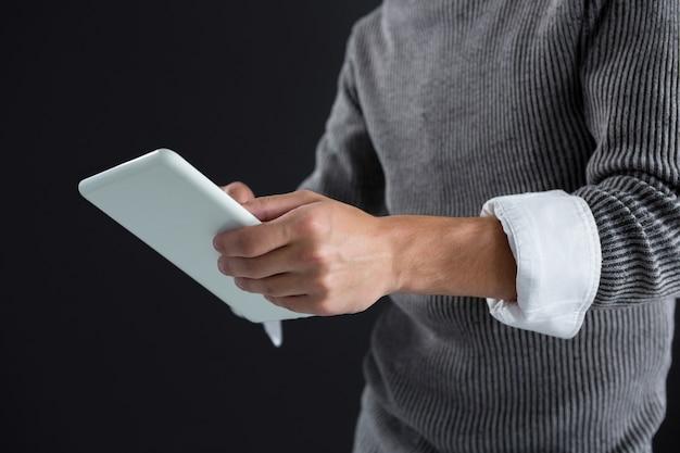 Androgynous man using digital tablet against black wall
