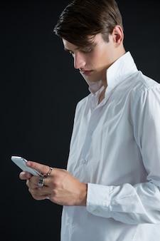 Андрогинный мужчина с помощью мобильного телефона