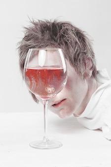 Андрогинная женщина с короткой стрижкой и белой футболкой смотрит в стакан, полный растекающейся по воде крови.