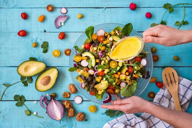 И женщины, поливающие свежий салат желтым соусом на синем фоне