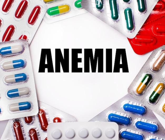 Anemia is written on a light background surrounded by multi-colored packages with pills. medical concept