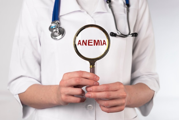 Anemia word through magnifier in hand of doctor