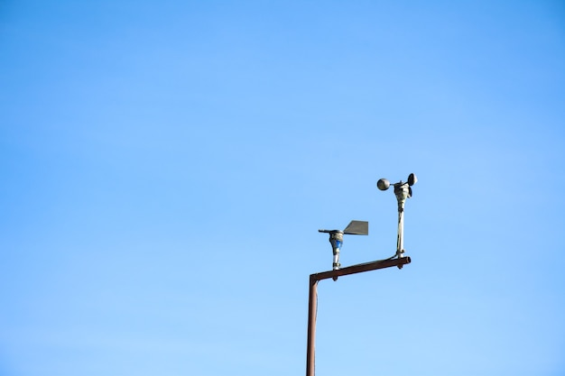 Анемометр в метеорологической станции на фоне голубого неба.
