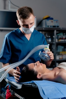 Anesthesiologist making ingalation anesthesia for patient. doctor puts a mask on the patient before starting operation