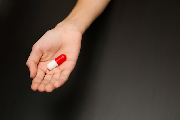 Anesthetic medicine pill capsule lies in the hand of a young man