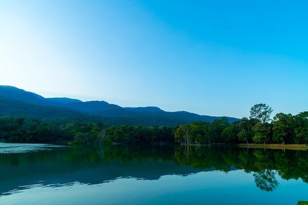 숲이 우거진 산과 황혼의 하늘이 있는 치앙마이 대학교의 앙 깨우 호수