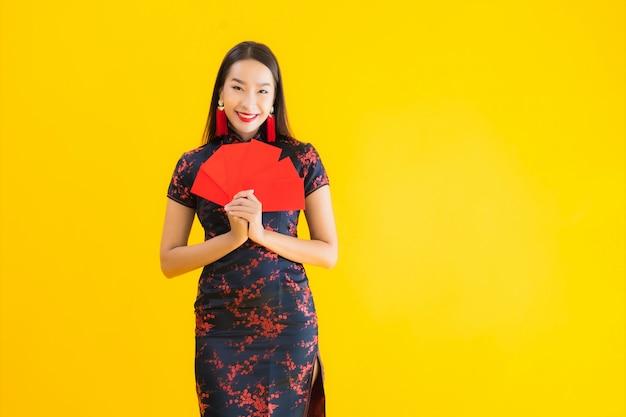 肖像画の美しい若いアジアの女性は、ang paoのチャイナドレスや現金で赤い文字を着る