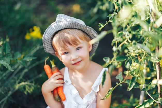 帽子とトマトangカメラ目線の周りに座っているカジュアルな服でかわいい男の子